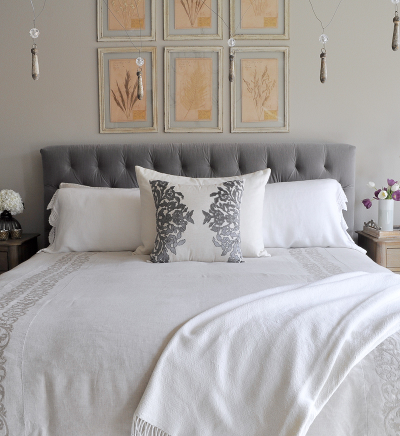 Bedroom Bed with Gray Fabric Tufted Headboard, Chandelier, Linen