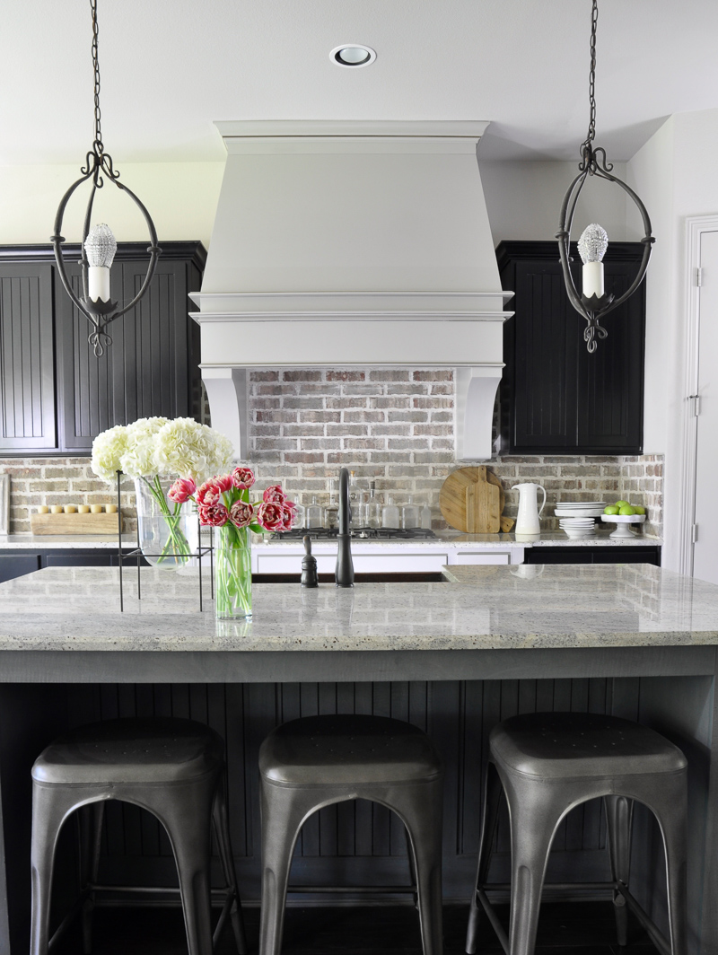 Kitchen with Brick Backsplash Large Venthood and Industrial Stools