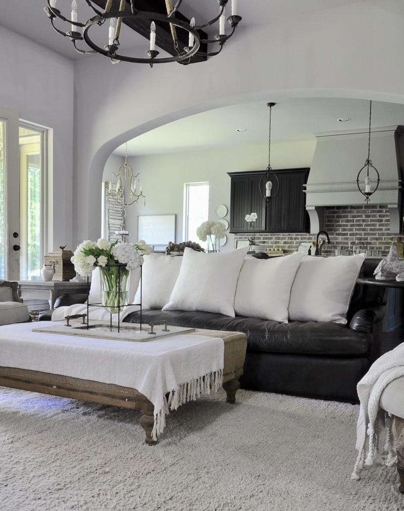 Neutral Living Room with Leather Sofa with Large White Pillows by Decor Gold Designs