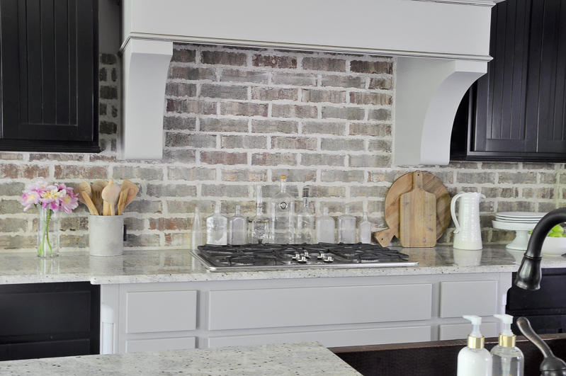 Gorgeous kitchen with brick backsplash large vent hood and black cabinets