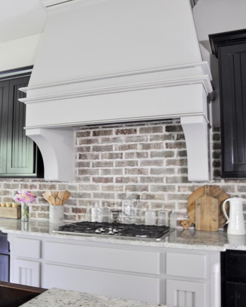 gorgeous vent hood and brick backsplash in bright kitchen decor