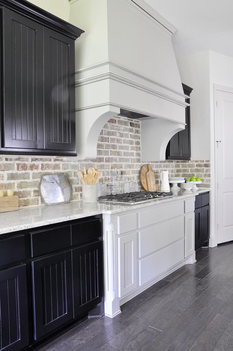Industrial Kitchen Brick Backsplash and Large Venthood