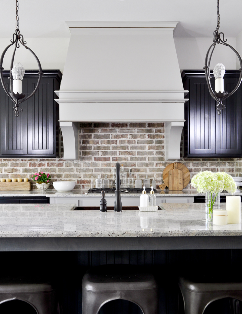 Kitchen with Statement Vent Hood and Black Cabinets decorated for summer