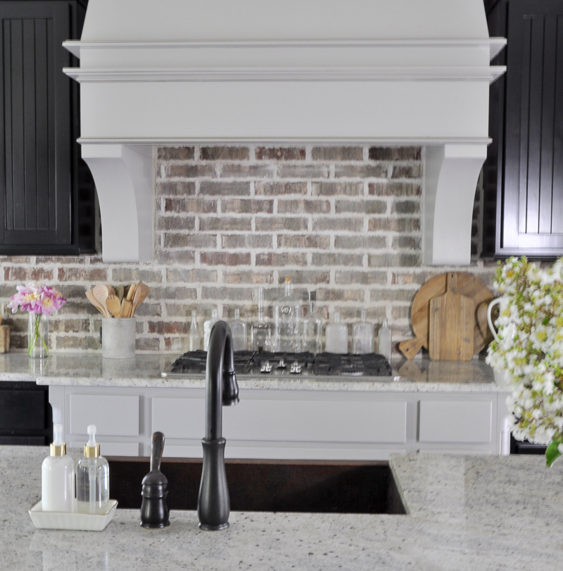 Statement vent hood and brick backsplash in beautiful kitchen