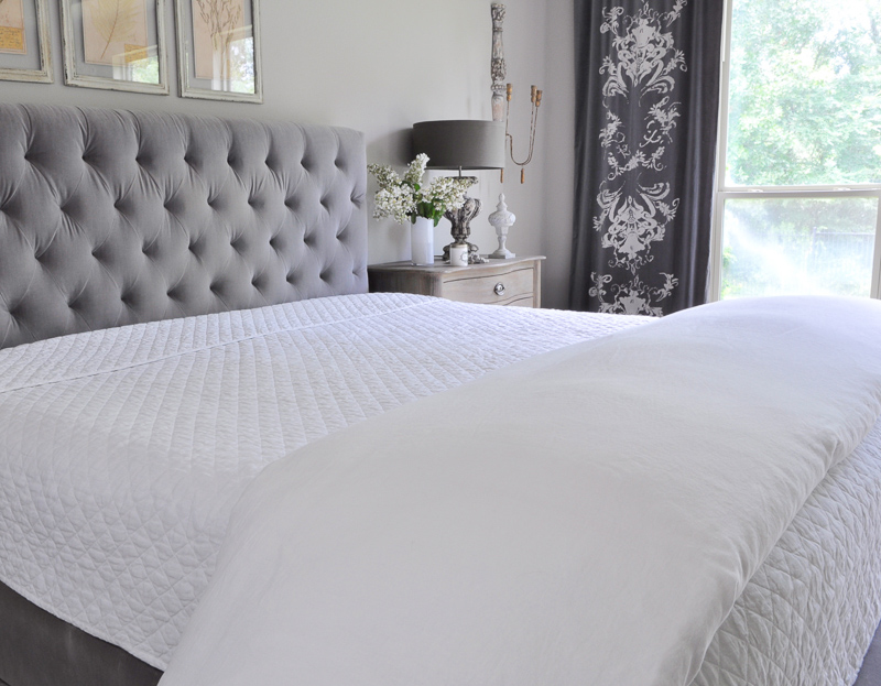 white linen bedding basics on beautiful gray tufted bed