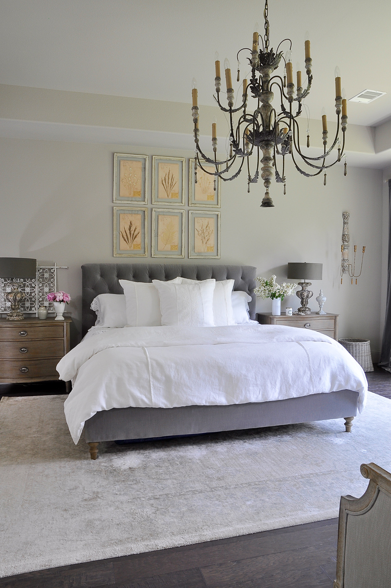 white and gray master bedroom with large chandelier and botan
