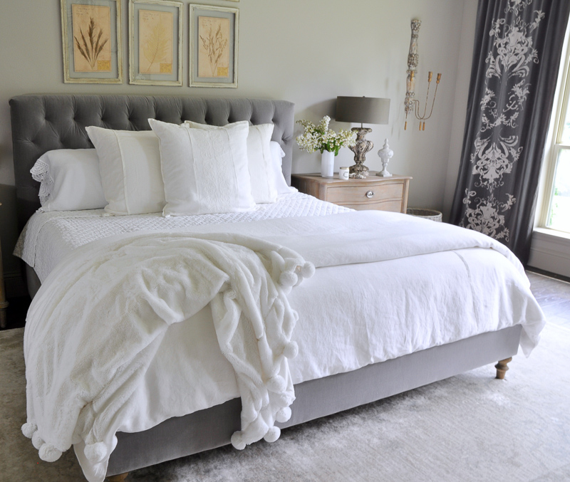all white bedding with linen pillows and gorgeous pom pom thr