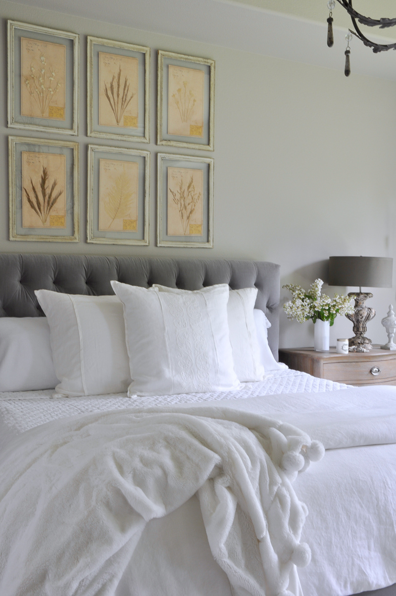 992 bedroom with botanicals above bed white layered linen and po