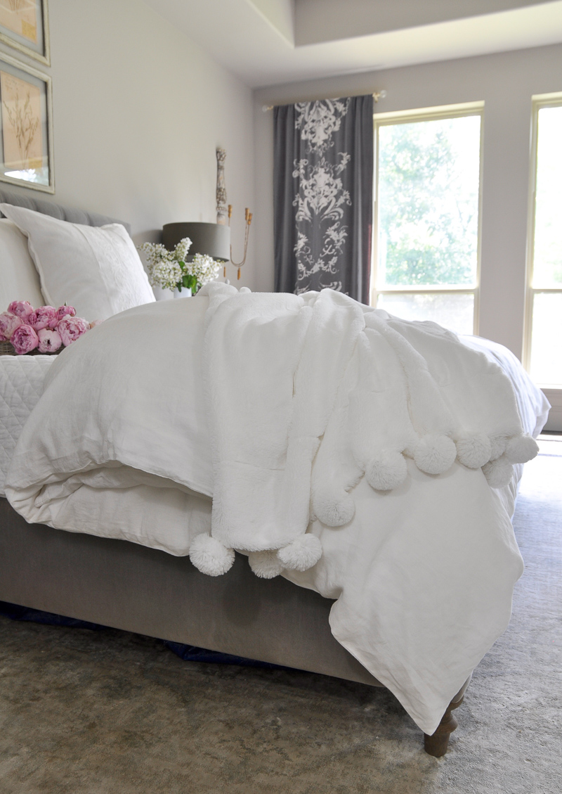 dreamy white pom pom throw in beautiful bedroom with vintage