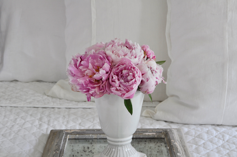 bedroom with pink peonies on beautiul tray on white linens
