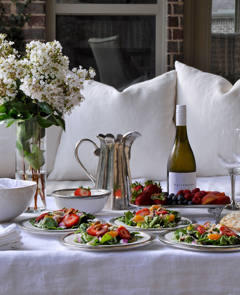 Outdoor patio dinner with flowers white dinnerware and pewter and beautiful salads and fruit-10