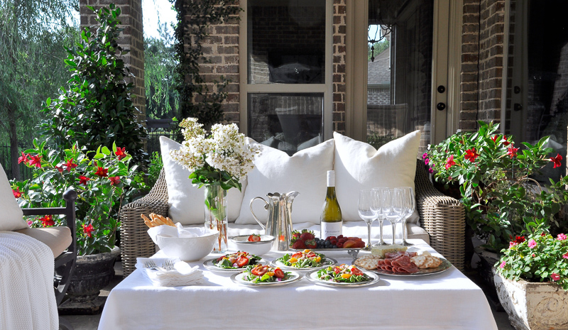 Outdoor patio dinner with flowers white dinnerware and pewter and beautiful salads and fruit-7