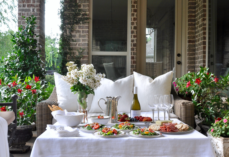 Outdoor patio dinner with flowers white dinnerware and pewter and beautiful salads and fruit-9