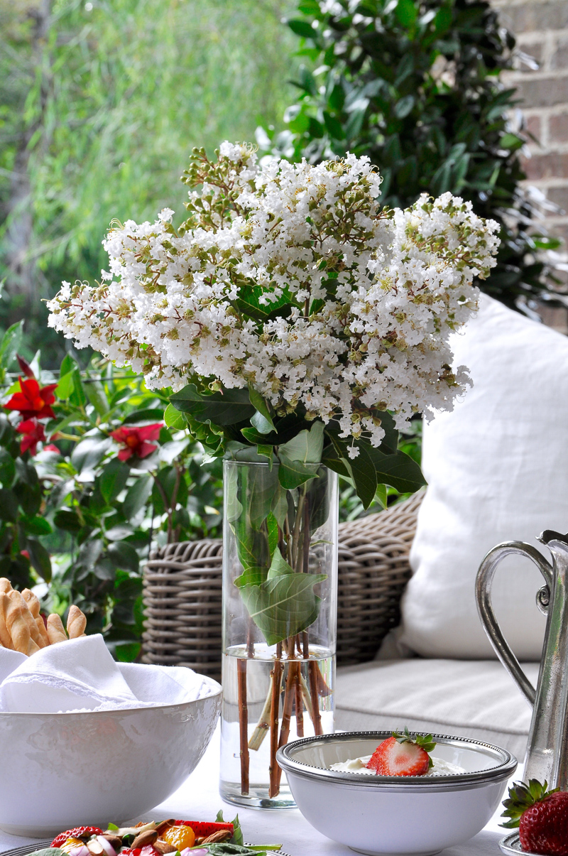 Summer outdoor patio party with flowers white linens and beautiful white and pewter dishes-4