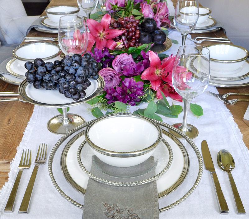 beautiful dining room set for a dinner party with ceramic and pewter dinnerware by arte italica and floral garland_