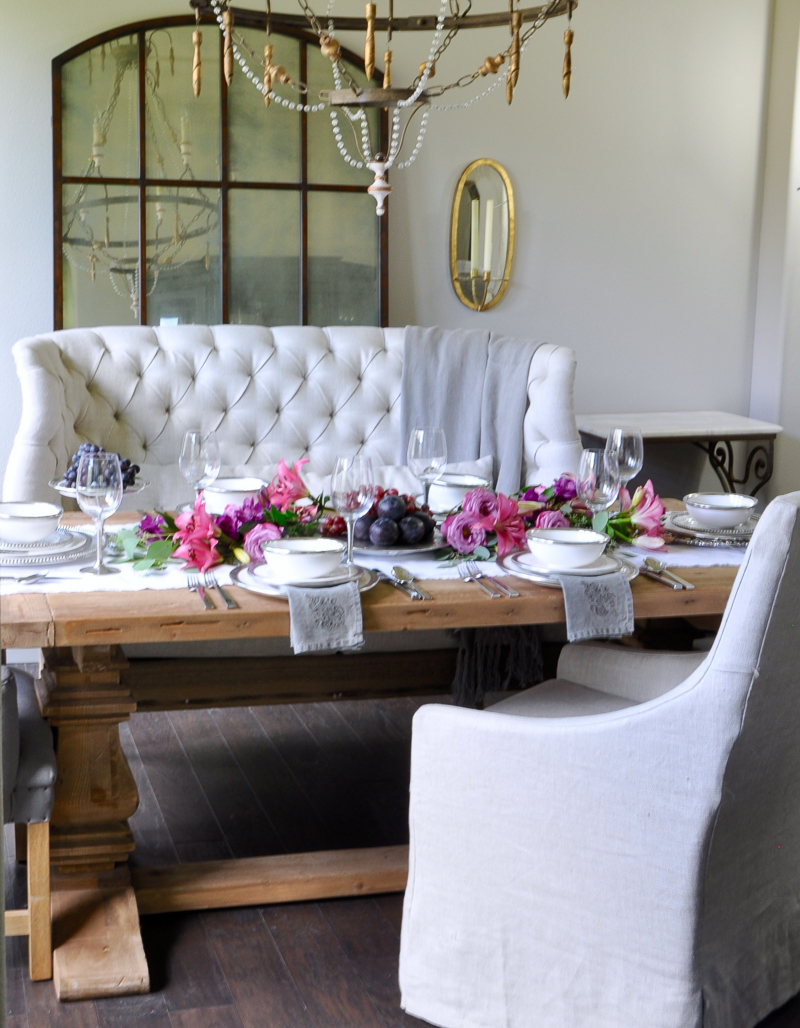 beautiful dining room set for a dinner party with pink and puple flowers