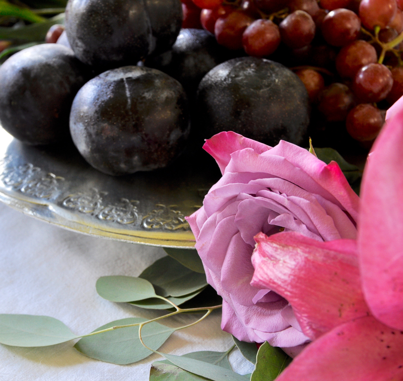 flowers and fruit add beauty to a centerpiece on a pewter serve=ing dish by arte italica
