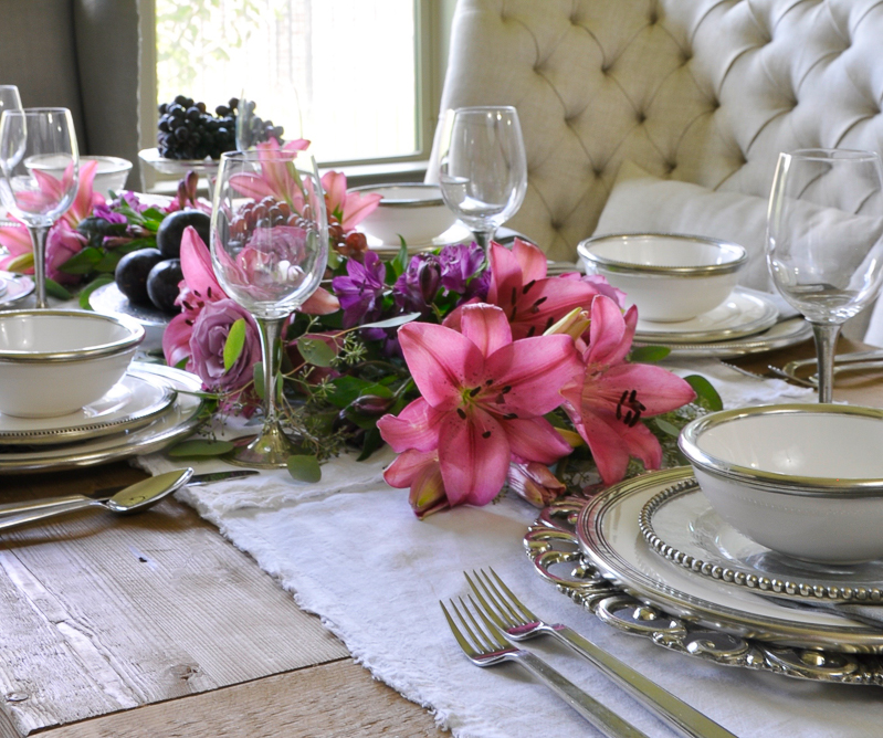 tablescape with fruit and flowers and white ceramic and pewter dishes by arte italica_