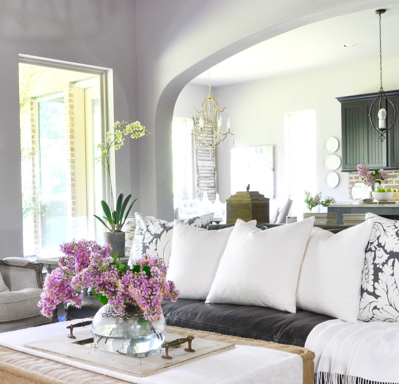 beautiful-white-accents-in-family-room-ottoman-with-vase-full-of-crepe-myrtle-clippings_