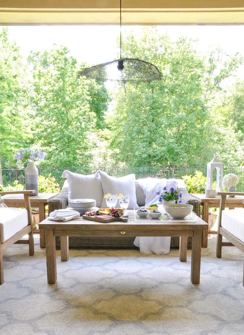 Beautiful outdoor space teak furnishings white pillows