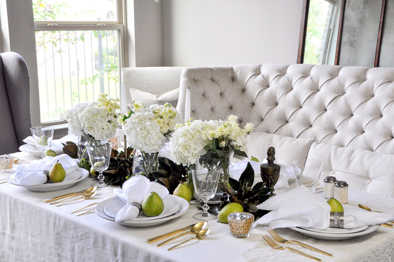 thanksgiving table ideas. Also, Magnolia Leaves At The Base Of Glass Vases Provide A Beautiful Contrast From Ivory Tablecloth And White Dinnerware. Additionally, Gold Votives Thanksgiving Table Ideas