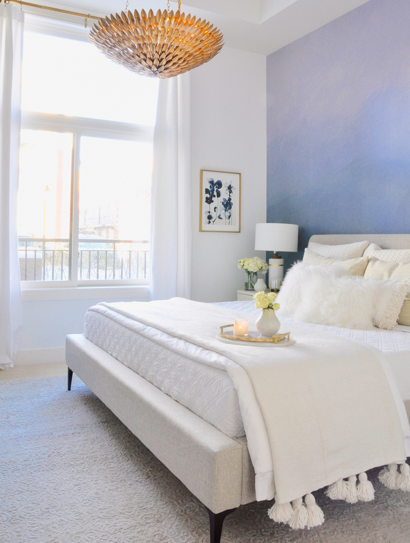 bedroom with layered white bedding and blue accent wall