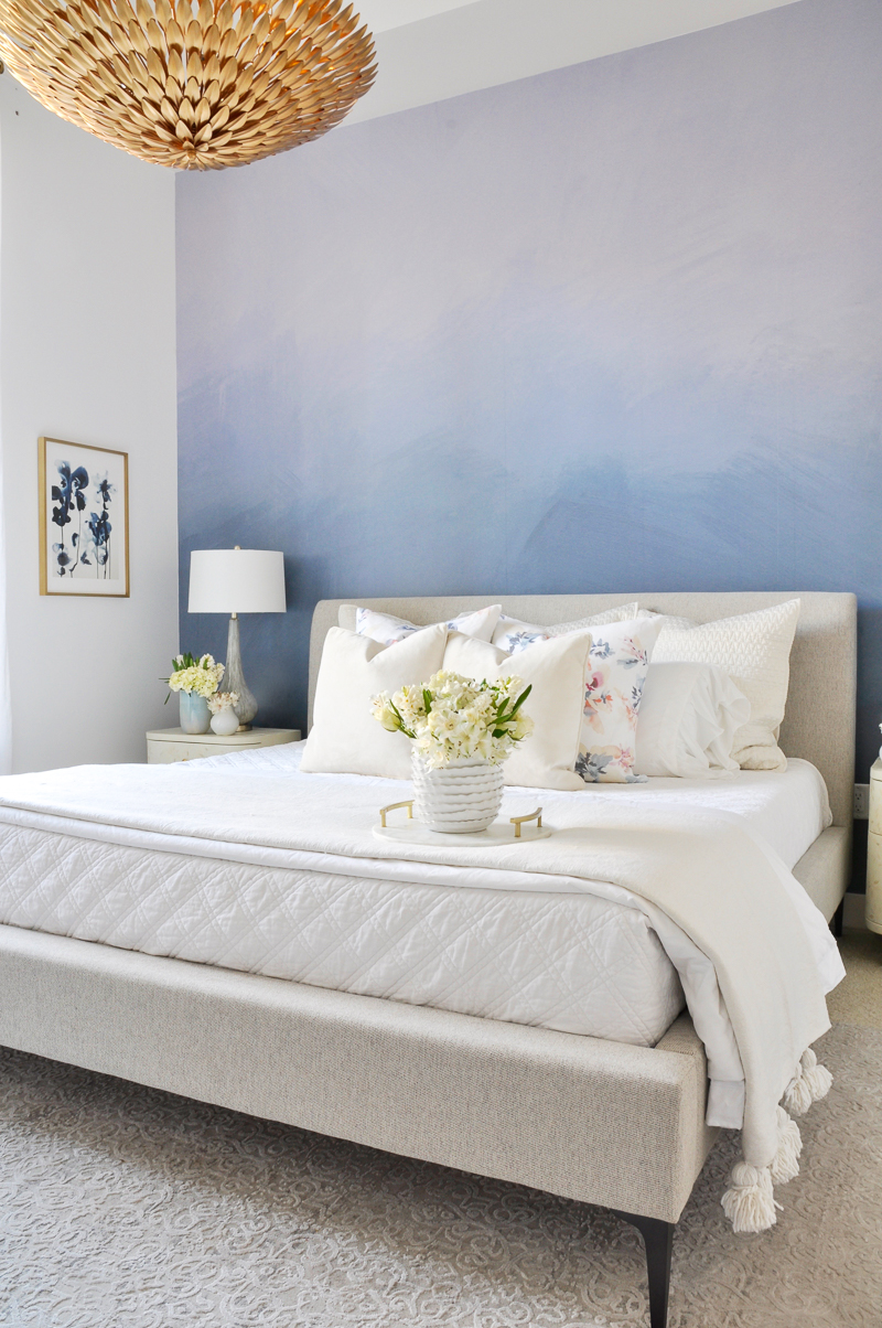 beautiful blue and white spring bedroom with white and floral bedding