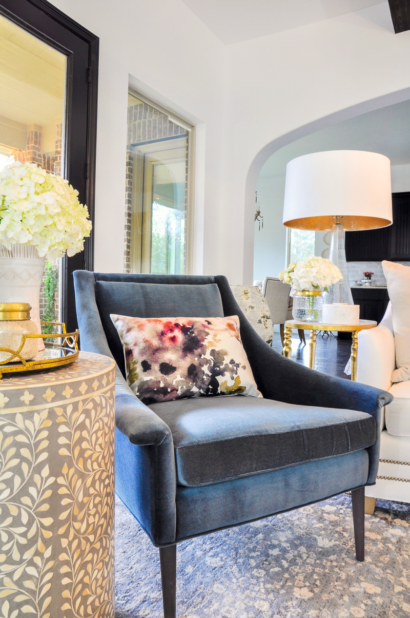 blue velvet chair and floral pillow