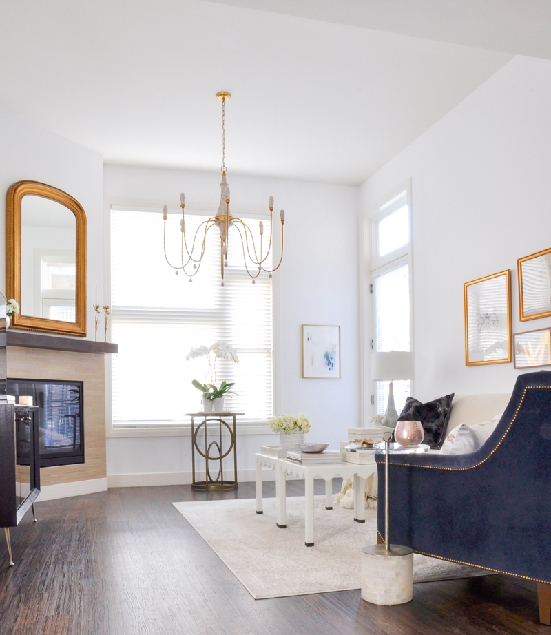 bright white living room with gold accents and blue velvet chair