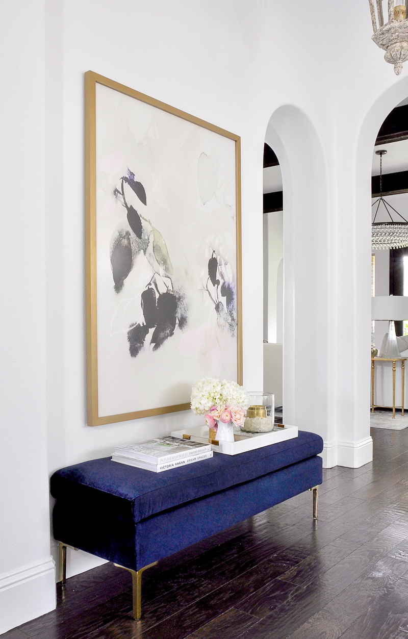 decorated home entry with blue velvet bench and beautiful large artwork