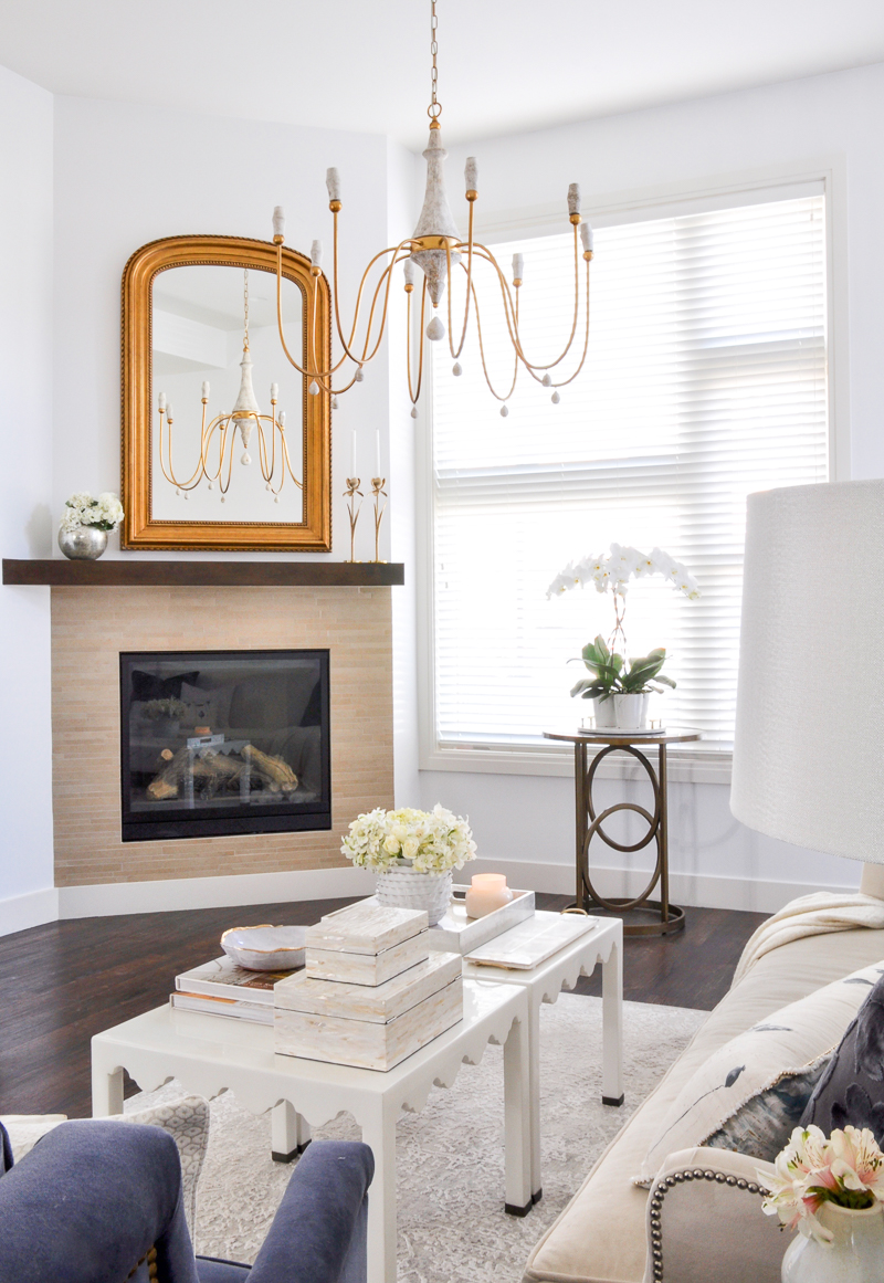 elegant arched gold mirror and chandelier in white living room
