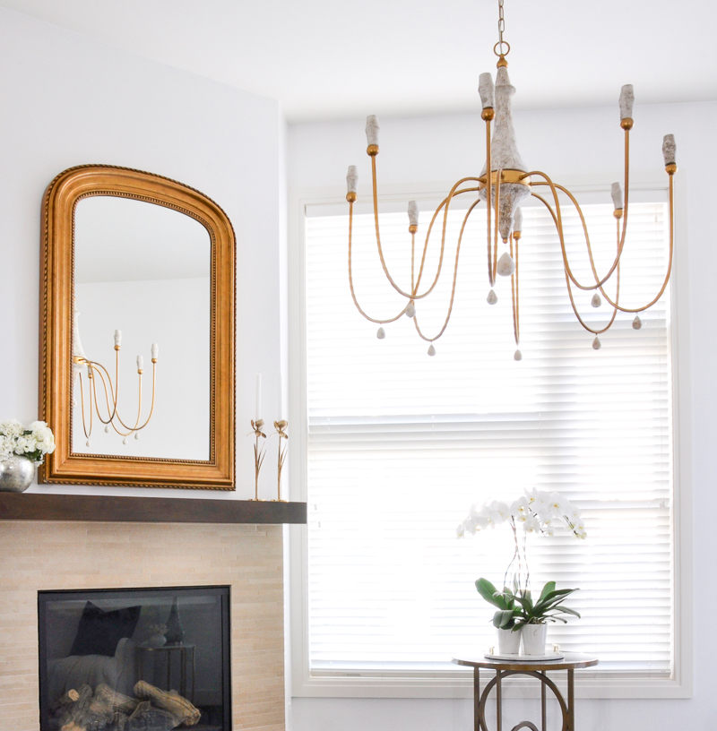 elegant arched gold mirror and chandelier over fireplace