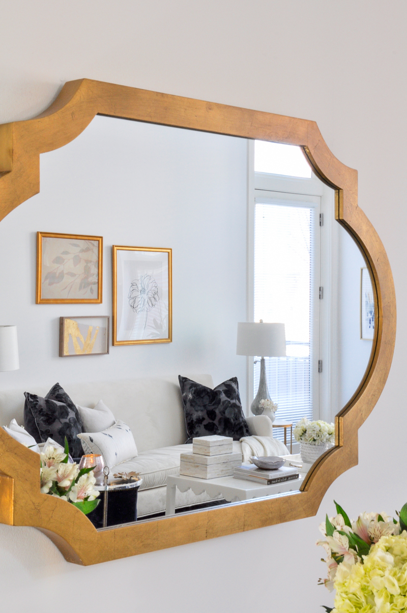 elegant gold mirror with beautiful white living room in reflection