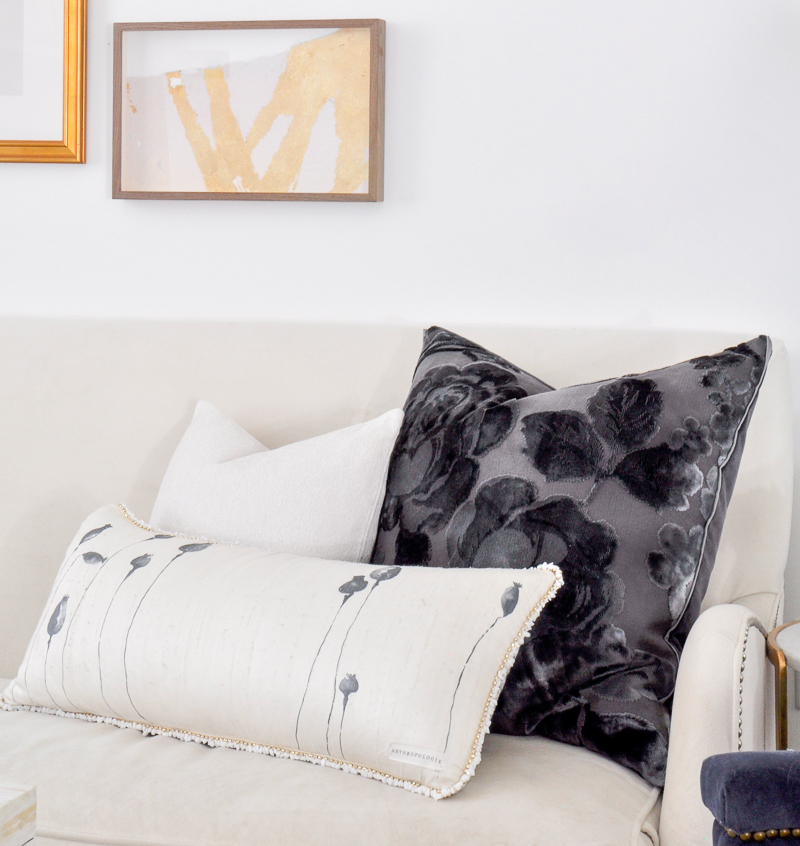 navy and white pillows on white sofa