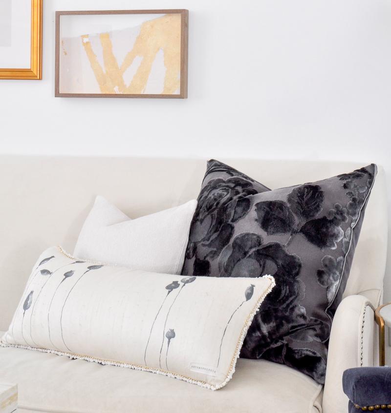 navy and white pillows on white sofa