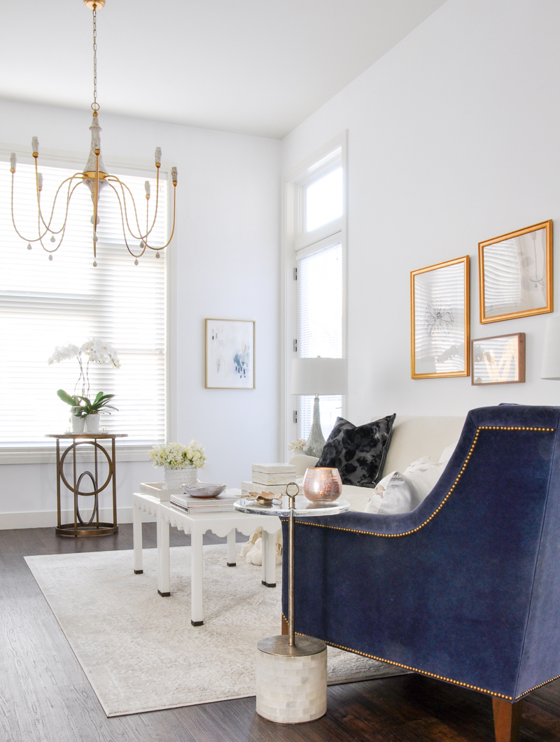 white living room with gold accents and blue velvet chair