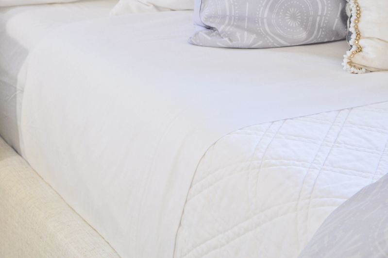 beautiful white bedding and coverlet