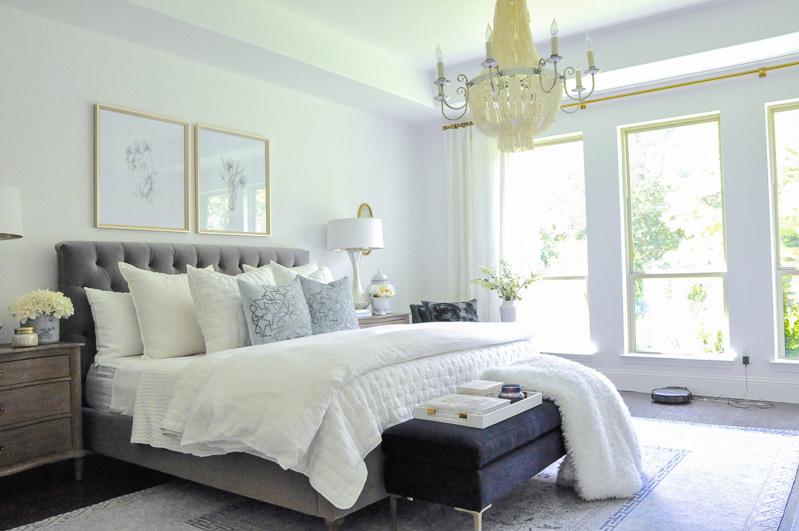 Bedroom gray bed white bedding robot vacuum in room