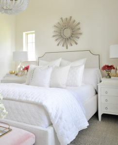 Beautiful white guest room starburst mirror