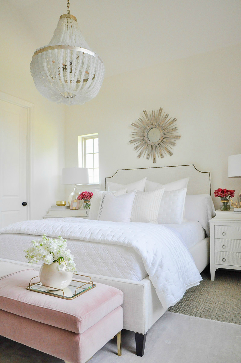Beautiful white guest bedroom starburst mirror beaded chandelier