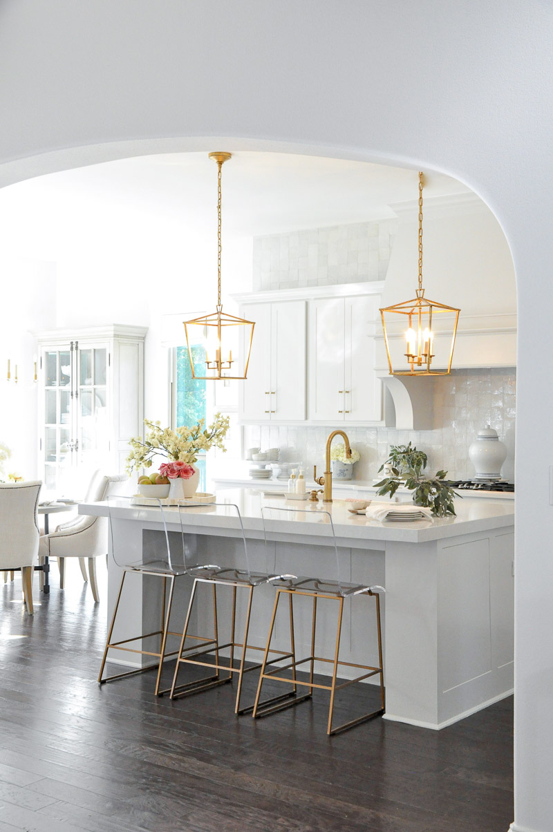 Bright white and light gray kitchen makeover reveal. Large statement vent hood. Gold accents