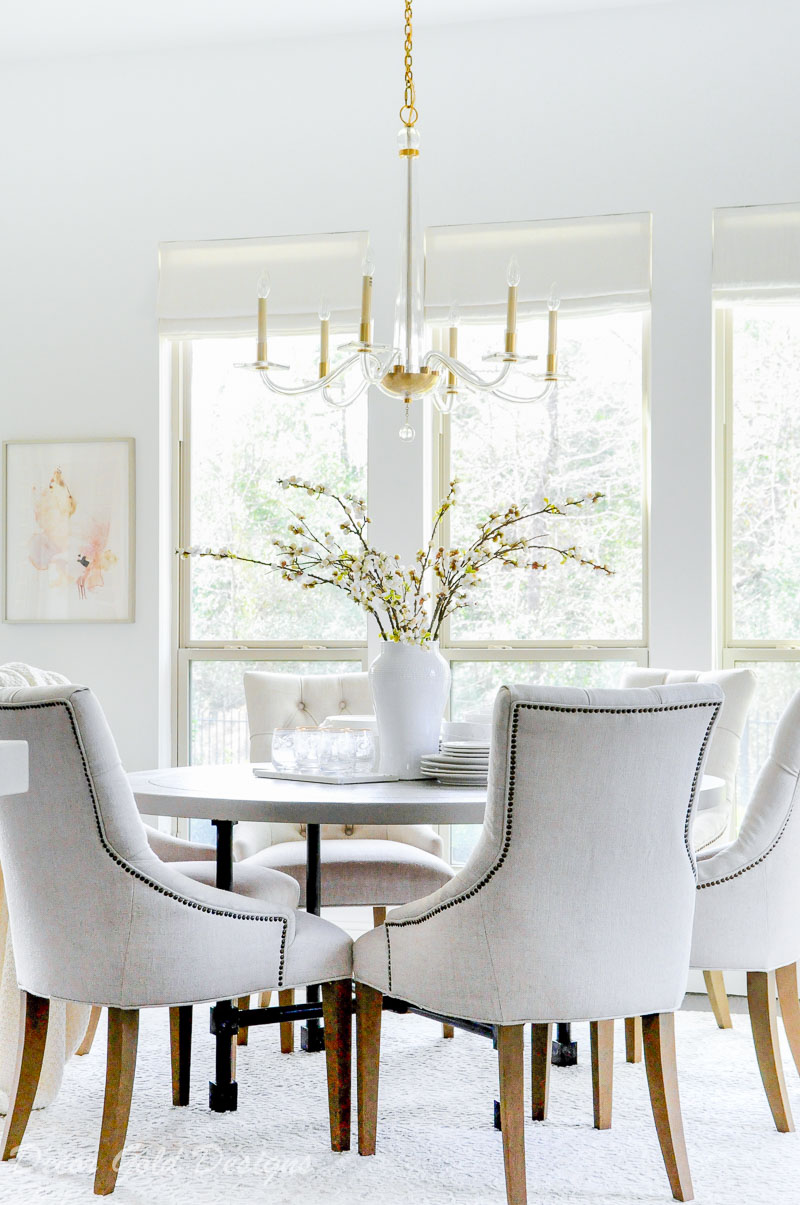 Breakfast room round table six chairs vase branches