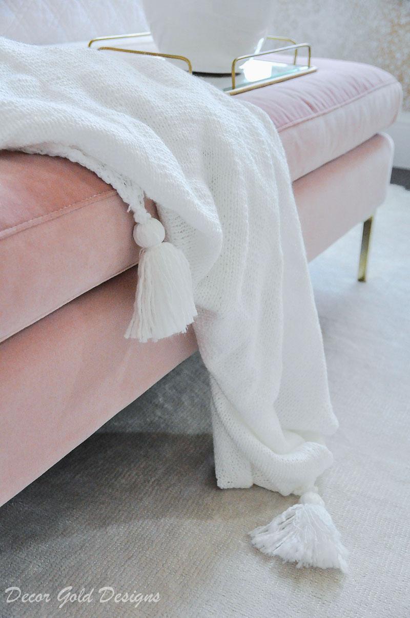 white tassel throw blanket pink bench