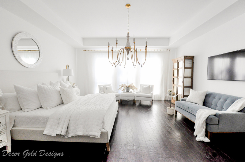 Master bedroom refresh white bed gold chandelier television blue sofa
