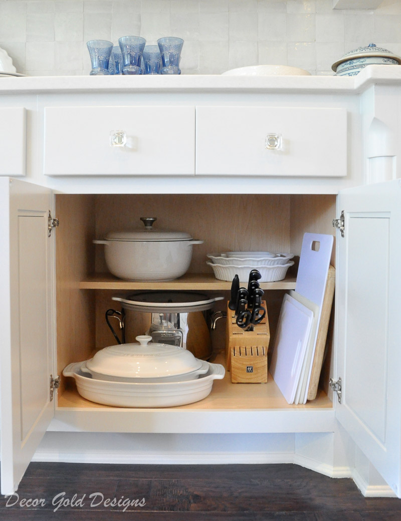 Kitchen organization project lower cabinet containing stoneware crockpot knife block cutting boards